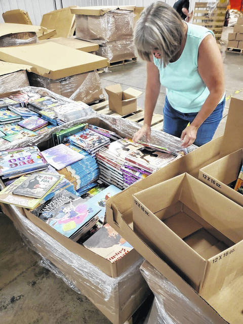 Jo Ellen Sherow, program manager for Kids on Campus, helps to sort through the books.