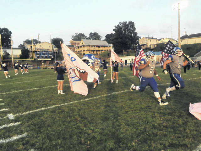 The Gallia Academy Blue Devils enter Memorial Field with American Flags on Friday night. (Bryan Walters | OVP Sports)
