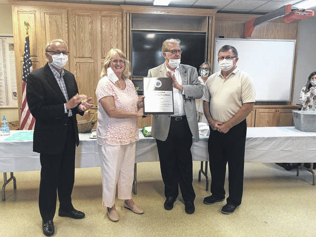 Karen Sprague, second from left, Gallia's first county administrator, is presented with a plaque recognizing her work upon her retirement last month. Also pictured, Gallia County Commissioners David Smith, Harold Montgomery and Brent Saunders. (Courtesy)
