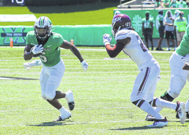 Marshall running back Sheldon Evans (5) tries to elude an Eastern Kentucky defender during the first quarter of a Sept. 5 football game at Joan C. Edwards Stadium in Huntington, W.Va.