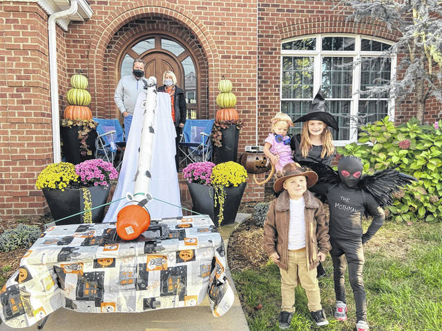 "On Friday evening, trick-or-treaters across Gallia County set out for some normalcy and some candy. With a few modifications, holiday traditions carried on, including at the home of Brent and Shawn Saunders on Third Avenue in Gallipolis. With safety, and fun, in mind, the couple constructed a candy dispenser out of a 10-foot piece of four-inch PVC plastic pipe, allowing trick-or-treaters to place their buckets at the bottom, awaiting a deposit of candy which slid down from the top. Visitors were also greeted with a sign that read, ""Trick or treat! Stand six feet. We'll give you something sweet."" Pictured are the couple with their grandchildren Rylee Jo and Austin (Mothman) Saunders, Benjamin and Parker Noe. According to Brent, the oversized candy dispenser was a hit with trick-or-treaters. (Courtesy)"