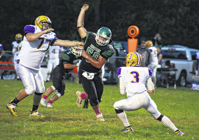Eastern senior Will Oldaker (50), pressures Southern quarterback Chase Bailey (3), during the Eagles' 42-0 victory on Friday in Tuppers Plains, Ohio.