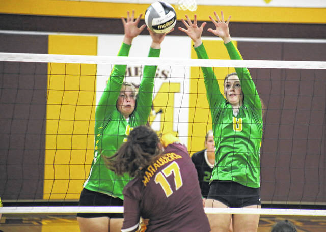 Eastern senior Tessa Rockhold (left), alongside teammate Olivia Barber (8), blocks a Katie Hawkins (17) spike attempt, during the Lady Eagles' 3-0 victory on Monday in Rocksprings, Ohio.