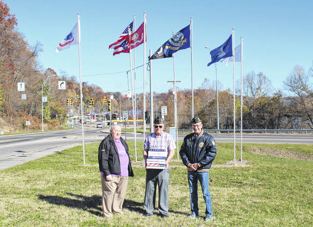 Dan Morris recently donated new flags in memory of his brother Robert B. Morris to Drew Webster American Legion Post 39 for the display at the Bridge of Honor. Pictured with Morris are Legion member Steve VanMeter and Commander John Hood.