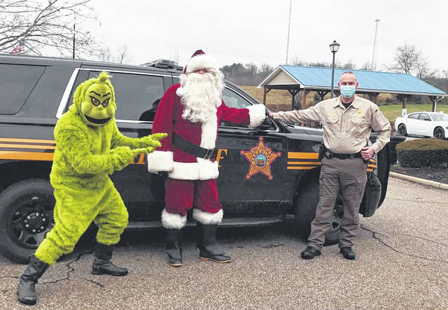 Gallia Sheriff Matt Champlin, pictured far right, along with Santa Claus and The Grinch, recently spent the afternoon visiting residents of long-term care facilities in the area. The visits, meant to spread a little holiday cheer, were safely done from outside the windows of residents. (Gallia Sheriff Facebook Page | Courtesy)