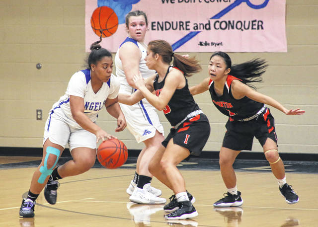 Gallia Academy junior Asia Griffin, left, dribbles past a pair of Ironton defenders during the first half of Thursday night's girls basketball contest in Centenary, Ohio.