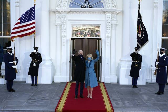 President Joe Biden and first lady Jill Biden wave as they arrive at the North Portico of the White House, Wednesday, Jan. 20, 2021, in Washington. (AP Photo/Alex Brandon, Pool)