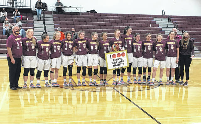 Members of the Meigs girls basketball team present Mallory Hawley with a game ball after surpassing 1,000 career points, during the Lady Marauders' 52-49 victoy on Tuesday in Rocksprings, Ohio.