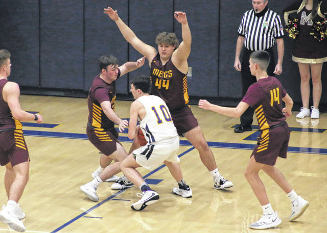Meigs defenders Ethan Stewart and Andrew Dodson (44) apply pressure to a Wellston player during the first half of Monday night's Division III sectional tournament game at WHS in Wellston, Ohio.