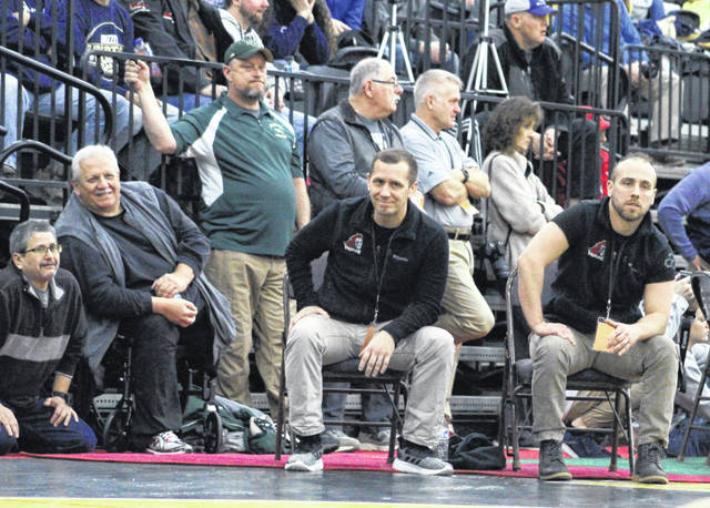 Point Pleasant wrestling coach John Bonecutter, middle, looks on with his brother David, right, during a match at the 2020 Class AA-A wrestling championships held at Mountain Health Arena in Huntington, W.Va.