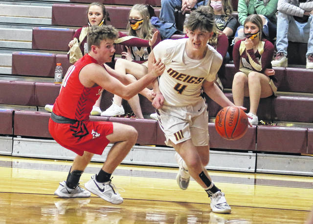 Meigs freshman Brayden Stanley (4) dribbles past Jackson defender Holden Blankenship during the second half of Wednesday night's boys basketball contest in Rocksprings, Ohio.