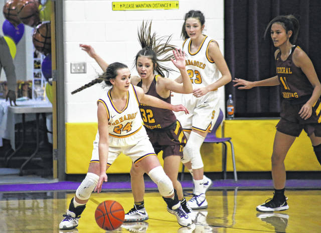 SHS freshman Kass Chaney (24) drives past Federal Hocking senior Paige Tolson (32), during the Lady Lancers' 56-33 victory on Thursday in Racine, Ohio.