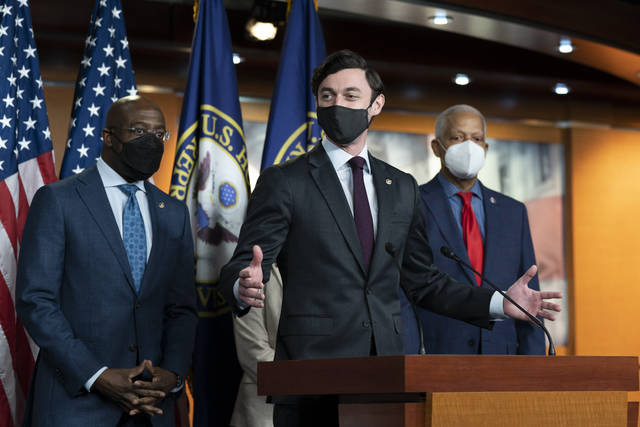 Sen. Jon Ossoff, D-Ga., center, speaks accompanied by Sen. Raphael Warnock, D-Ga., left, and Rep. Hank Johnson, D-Ga., during a news conference, before the vote on the Democrat's $1.9 trillion COVID-19 relief bill, on Capitol Hill, Wednesday, March 10, 2021, in Washington. (AP Photo/Alex Brandon)