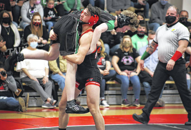 Point Pleasant's Mitchell Freeman lifts a Winfield opponent up for a slam during the season-opening quad on March 3 in Point Pleasant, W.Va.