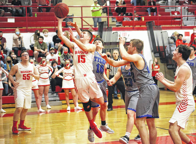 Wahama sophomore Josiah Lloyd (15) slips between defenders for a layup, during Tuesday's LKC bout at Gary Clark Court in Mason, W.Va.