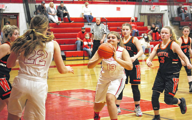 Wahama's Morgan Christian (13) dishes to teammate Mikie Lieving (22), during the second half of the Lady Falcons' 61-39 victory on Monday in Mason, W.Va.