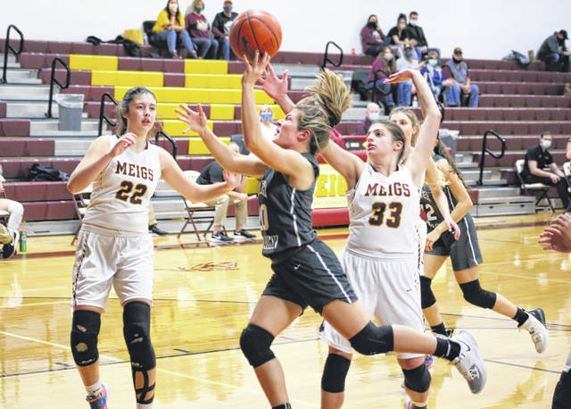 River Valley junior Lauren Twyman releases a shot attempt between Meigs defenders Rylee Lisle (22) and Hannah Durst (33) during a Dec. 21, 2020, girls basketball contest at Meigs High School in Rocksprings, Ohio.