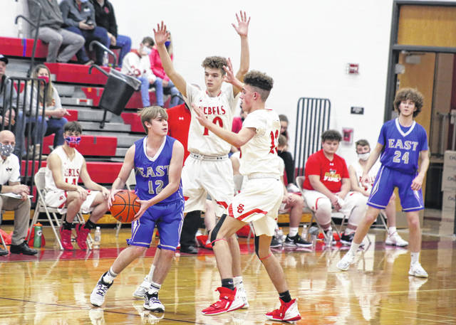 South Gallia defenders Jaxxin Mabe (10) and Brayden Hammond (20) trap a Sciotoville East player during a Dec. 29, 2020, boys basketball contest in Mercerville, Ohio.