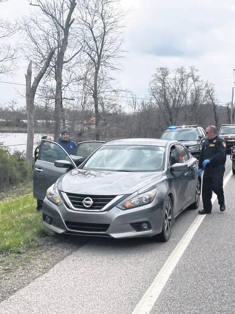 Law enforcement officials surround a car driven by Terry Bell which was stopped on State Route 7 Thursday afternoon. Bell was taken into custody at the scene after an alleged incident in West Virginia.