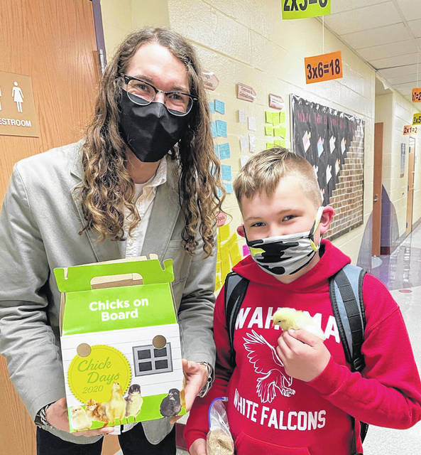 New Haven Elementary School fourth grader Ryan Gibbs is shown holding the chick he took home Thursday, following a special project at the school. Also pictured is school social worker Elijah McClanahan.