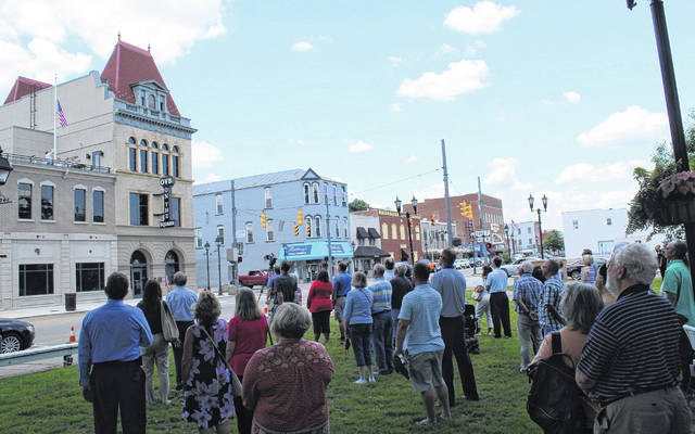 The Gallia County Veterans Honor Guard raises the American Flag at OVB on the Square in the distance.