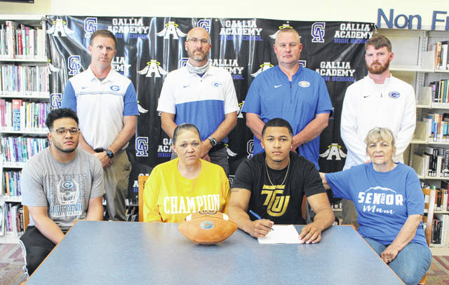 Gallia Academy senior James Armstrong, seated second from right, will be continuing his football career after signing with Tiffin University. Armstrong, a 4-year letterwinner, 3-time All-OVC and 2-time All-Ohio recipient in Division IV, plans to major in Business and currently possesses a 2.87 grade-point average. Armstrong is joined by family members Eli Miller (brother), Lori Skidmore (mother) and Marilyn Massie (grandmother) at the table. Standing in back are GAHS Athletic Director Adam Clark, GAHS football coach Alex Penrod, GAHS assistant Jared McClelland and GAHS assistant Cody Call.