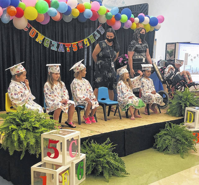Guiding Hand Preschoolers prepare to graduate at a ceremony held in their honor and were joined by staff onstage to celebrate their student achievements. Pictured are Jaxon, Sable, Haven, Daisy, Isabella, Harley, Jodi Newell, teacher and Kayla Ingles, aide.