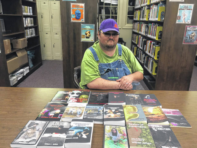 Pictured is Will Jeffers with 19 of his published books.