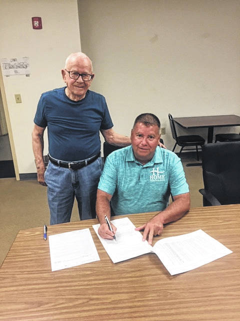Randy Pierce of Home National Bank (seated) is pictured with Mayor Fred Hoffman. Pierce is signing the deed donating property to the village of Middleport. The property is located at the corporation limit where the bank provided a Welcome to Middleport sign.