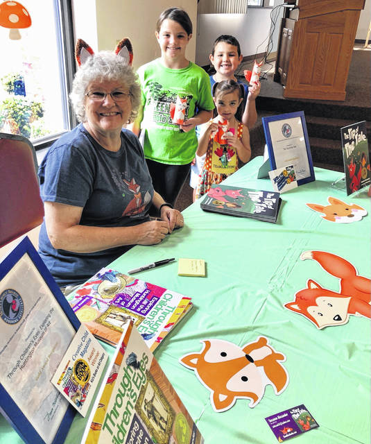 Author Suzanne Alexander signs copies of her books on Monday after story time at Bossard Library. Following a reading of The Tip of the Tale, children completed a fox-themed craft.