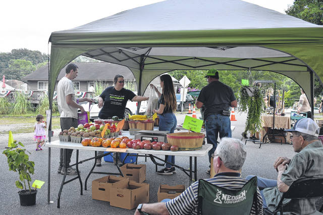 Visitors to Raised Around Rio Farmer's and Artisan Market pick up produce on a recent Wednesday evening.