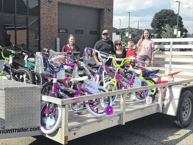 Bossard Library Youth Services Coordinator Rachael Barker, left, stands with Brian and Chelle Modrzynski, right, along with their two youngest children, Bryson and Addison, as they drop off over 20 new bicycles at Bossard Library. These donated bicycles were awarded through prize drawings among children who had participated in this year's Summer Reading Program.
