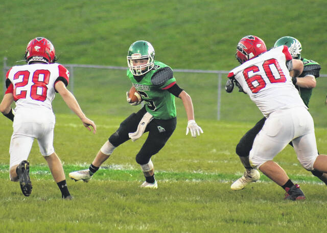 Eastern senior running back Bryce Newland (6) looks to split a pair of Caldwell defenders during the first half of Friday night's football game at East Shade River Stadium in Tuppers Plains, Ohio.