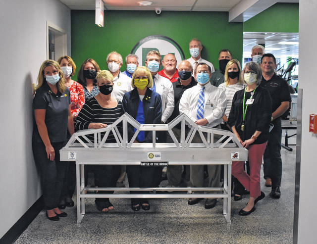 Members of the Gallipolis and Point Pleasant Rotary clubs, pictured, gathered Wednesday with the Battle of the Bridge Rotary traveling trophy. Also pictured, personnel from Pleasant Valley Hospital which commissioned the latest version of the trophy in 2019 and is also sponsoring Friday's football game between PPHS and Gallia Academy.