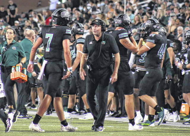First-year Ohio University head football coach Tim Albin, middle, has a word with quarterback Kurtis Rourke (7) coming off the field during a Sept. 4 football game against Syracuse at Peden Stadium in Athens, Ohio.