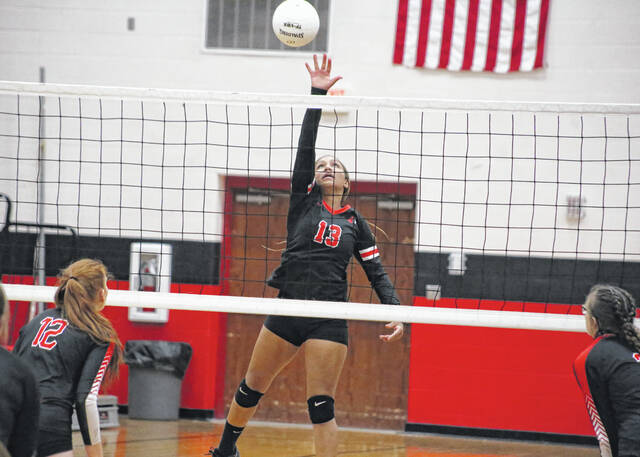Point Pleasant junior Kierra Smith (13) jumps to tip the ball against the Wayne Lady Pioneers in game one of the tri Thursday evening in Point Pleasant, W.Va.
