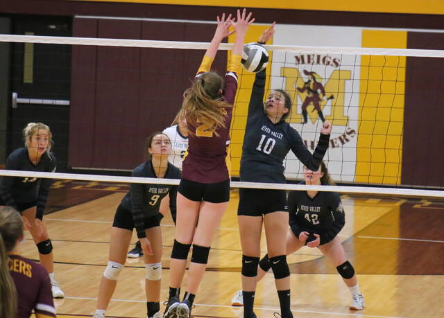 River Valley junior Riley Bradley (10) gets a spike attempt down despite a block by Meigs senior Andrea Mahr (2) during Tuesday night's TVC Ohio volleyball match in Rocksprings, Ohio.