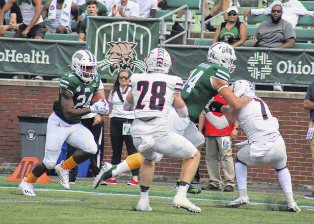 Ohio running back De'Montre Tuggle (24) follows the block of teammate Adam Luehrman while trying to gain extra yardage during a Sept. 11 football contest against Duquesne at Peden Stadium in Athens, Ohio.