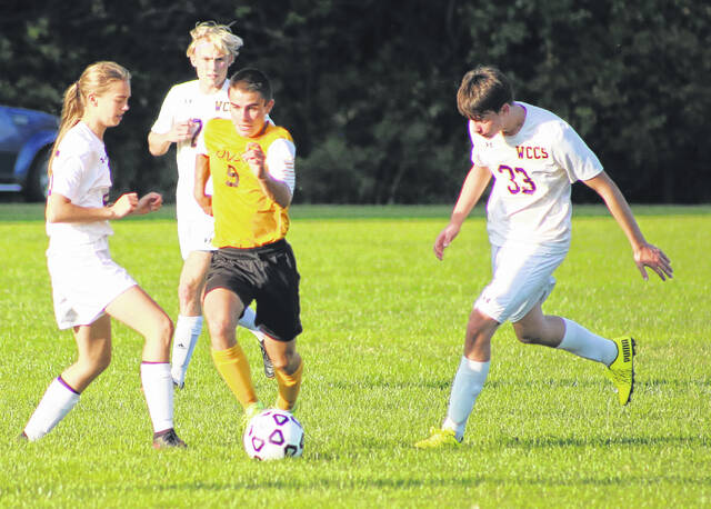 Ohio Valley Christian junior Bradley Haley dribbles the ball by three Wildcat defenders during a soccer game Monday evening in Gallipolis, Ohio.