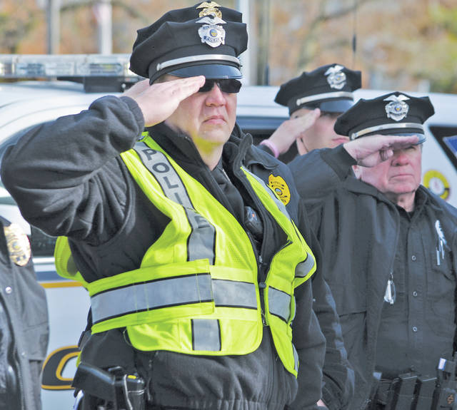 Auxiliary police officer Bob Rudolph offers a salute at the Amherst Veterans Day ceremony, where he worked a special detail.