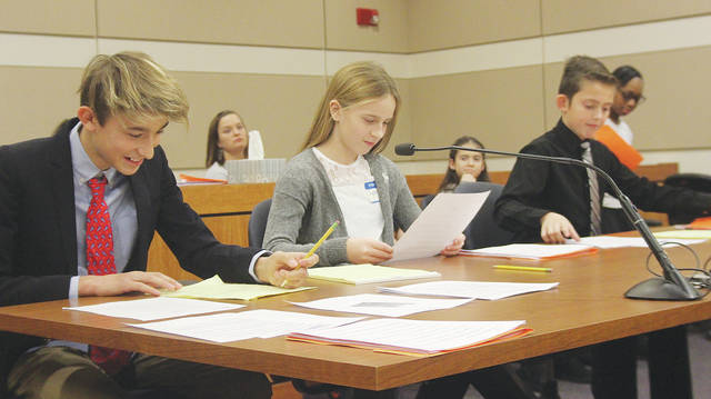 Amherst Junior High School sixth-graders Devin Ramirez, Sydney Alto, and Zachary Grumble work as the defense team Dec. 8 in this year's Lorain County mock trial.