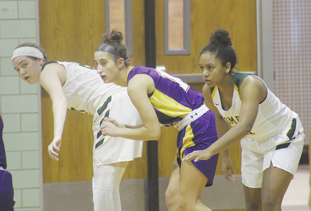 Amhert's Kate Iliff and Faith Lewis flank Lakewood's Courtney Ribar Saturday during the Comets' 61-54 overtime loss.