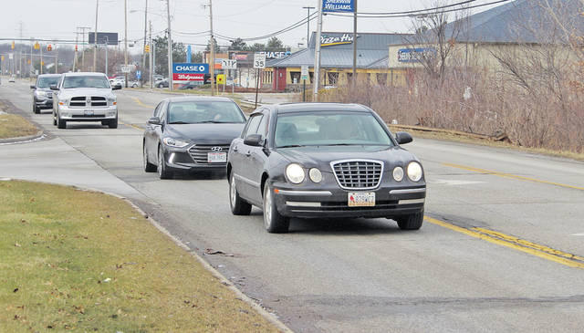A line of cars travels east down Cooper Foster Park Road from Rt. 58. The stretch is due for repaving in 2019 but complaints abound now about its condition.