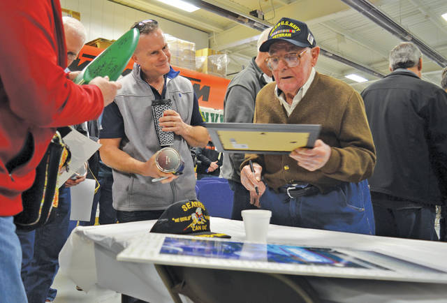 Motorcycle legend John Penton signs autographs for a long line of admirers after an 50th anniversary opening ceremony Saturday at KTM North America's warehouse on Milan Avenue.