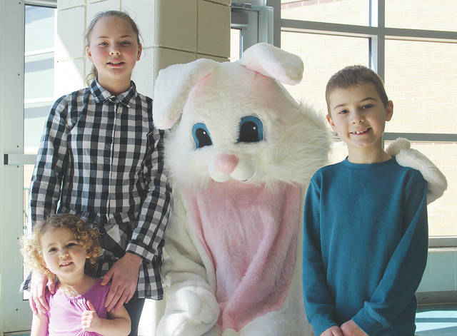 Evelyn Mary, Aubrynn, and Seth Reichle of New Russia Township say hello to the Easter Bunny at a breakfast organized by Amherst Steele cross country runners.