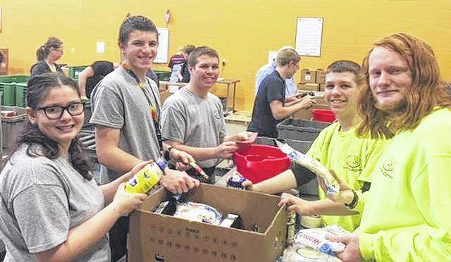 Students Sophia Couch, Don Sabella, Billy Keller, Tommy Keller, and Bailey Zorn enjoy their time at Second Harvest Food Bank.