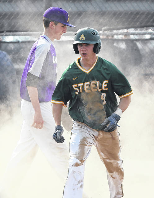 Ryan Glowacki of Amherst emerges from a cloud of dust after scoring the game's only run against Avon on Thursday.
