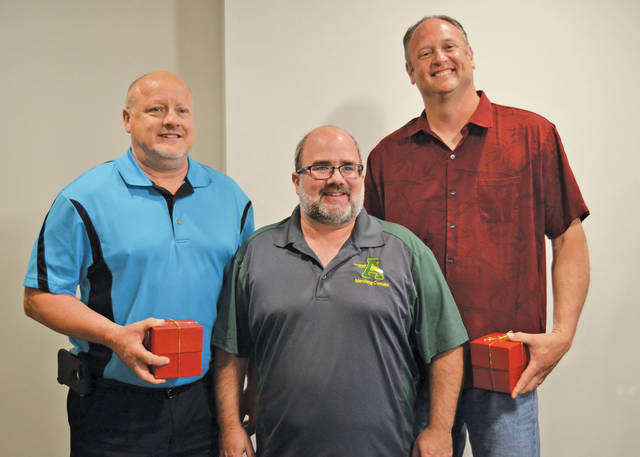 Jeff Rakar and Scott Douglass pose with Amherst Marching Comets director Chris Barbaro and their Crystal Apple Awards.