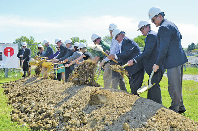 Education officials use silver shovels to turn dirt in a groundbreaking ceremony May 23 for Amherst's new Powers Elementary School on South Lake Street.