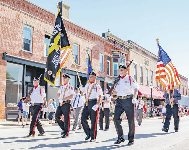 Flags held high, the Amherst Veterans Memorial Honor Guard nears the intersection of Park Avenue and South Main Street.